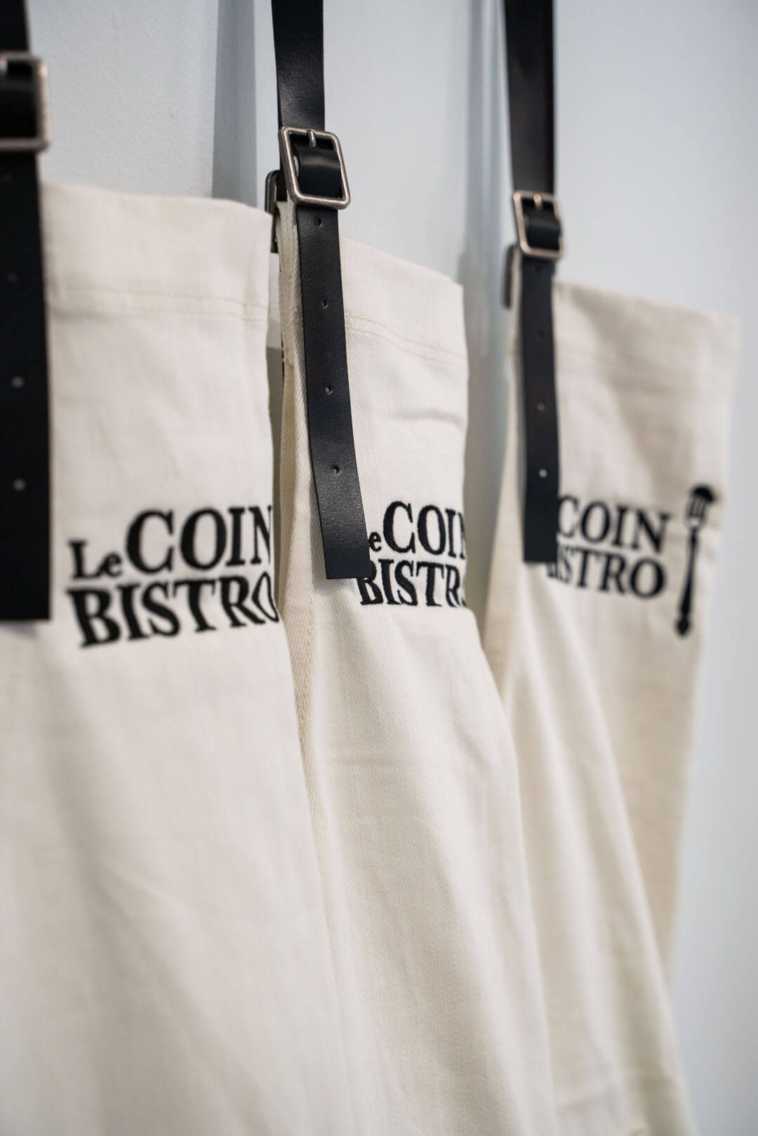 Le Coin Bistro aprons hanging on wall